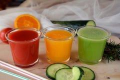 Verse sinaasappel, tomaat en komkommer smoothie op een glas Stock Afbeeldingen