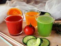 Verse sinaasappel, tomaat en komkommer smoothie op een glas Stock Afbeelding