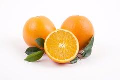 Verse sinaasappelen met de helft op een witte achtergrond Stock Afbeeldingen