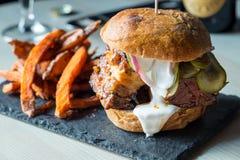 Verse Smakelijke Bacon Grote Hamburger met Fried Sweet Potatoes en Witte saus Stock Afbeeldingen