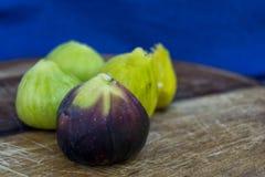 Verse smakelijke fig.vruchten op een houten plaat met een blauwe achtergrond Stock Afbeeldingen