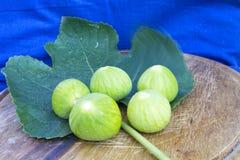 Verse smakelijke fig.vruchten op een houten plaat met een blauwe achtergrond Stock Foto