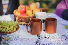 Verse smakelijke ontbijt, koffie, thee en vruchten op een wit wit kanttafelkleed op een lijst in de straat royalty-vrije stock fotografie