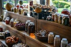 Verse smakelijke pompoenen en bewaard en ingelegde seizoengebonden groenten en honing in glaskruiken en op manden op bruin w stock fotografie