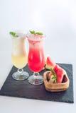 Verse smoothie in glas met gesneden stukken van watermeloen en meloen met munt op wit isoleerde achtergrond De zomerdranken Stock Fotografie
