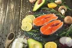 Verse stukken van zalmlapje vlees, forel, zalm, roze zalm Met ingrediëntengroenten, avocado, rozemarijn en broccoli Gezond en royalty-vrije stock foto