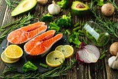 Verse stukken van zalmlapje vlees, forel, zalm, roze zalm Met ingrediëntengroenten, avocado, rozemarijn en broccoli Gezond en stock afbeelding