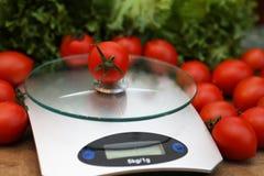 Verse tomaten bij keukenschalen het wegen Stock Afbeeldingen