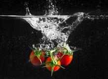 Verse tomaten die in water vallen Stock Foto