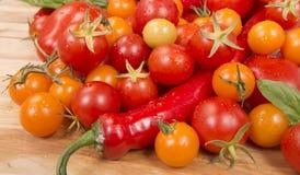 Verse tomaten en andere groenten die op scherpe raad morsen Stock Foto