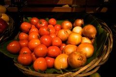 Verse tomaten en uienmand Stock Fotografie