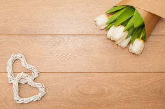 Verse tulpenbloemen en decoratief hart op houten planken Stock Foto