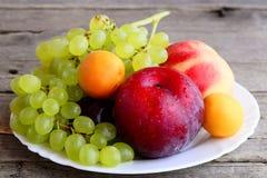 Verse vruchten assortiment De druiven bundelen, perzik, pruim, abrikoos op een witte plaat en een houten achtergrond close-up royalty-vrije stock afbeelding