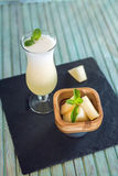 Verse witte smoothie in een glas met gesneden stukken van meloen en munt op een blauwe houten achtergrond De zomer koele dranken Royalty-vrije Stock Foto's