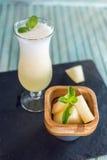 Verse witte smoothie in een glas met gesneden stukken van meloen en munt op een blauwe houten achtergrond De zomer koele dranken Royalty-vrije Stock Fotografie