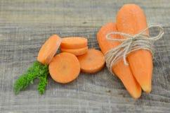 Verse wortelen en besnoeiingenplakken van wortelen op houten Royalty-vrije Stock Fotografie