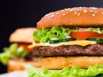 Verse yummy geroosterde burgers op zwarte achtergrond Vleespasteitje, tomaten, komkommer, sla en sesamzaden Snel voedsel royalty-vrije stock afbeeldingen