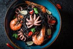 Verse zeevruchten zwarte die deegwaren van octopus en tijgergarnalen worden gemaakt royalty-vrije stock fotografie