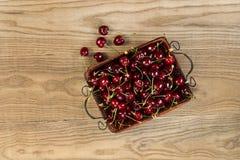 Verse Zwarte Kersen in mandplaats op Rustiek Hout Stock Fotografie