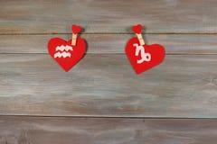 Verseau et Capricorne signes du zodiaque et de coeur Ba en bois Images stock