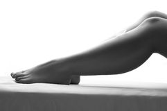 Versehen Sie das Lügen auf dem Bein einer Frau auf weißem Hintergrund mit Federn Lizenzfreie Stockfotografie