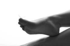Versehen Sie das Lügen auf den Fingern von weiblichen Füßen mit Federn Stockbild