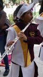 Versehen Sie das Marschmädchen mit einem band, das eine lange silberne Flöte spielt lizenzfreies stockfoto