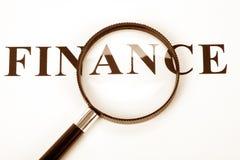 Versehen Sie Finanzierung und Vergrößerungsglas mit einer Überschrift Lizenzfreies Stockfoto