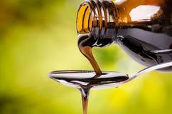 Versement d'un liquide sur une cuillère Fond vert normal Pharmacie et fond sain médecine Toux et drogue froide images stock