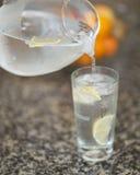 Versement d'un verre d'eau glacée Photos libres de droits