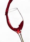 Versement d'un verre de vin rouge sur le fond blanc Images stock