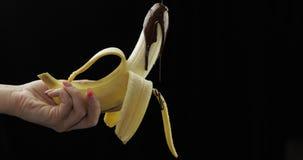 Versement d'une banane avec le sirop de chocolat fonc? fondu Fond noir banque de vidéos