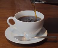 Versement d'une tasse de café d'une presse française photo stock