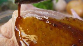 Versement de la marinade sur le poulet banque de vidéos