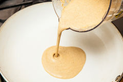 Versement de la pâte lisse de crêpes de quinoa dans une poêle Images libres de droits