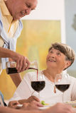 Versement de son verre de vin pendant un repas Photo stock