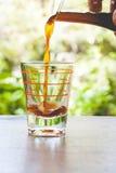 Versement outre du café dans un verre Photo stock