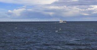 Versenden Sie im Meer mit Windmühle auf horizont Stockbilder