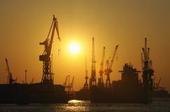 Versenden Sie im trockenen Dock und in den Kränen am Sonnenuntergang Stockfoto