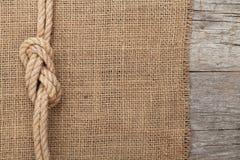 Versenden Sie Seil auf Holz- und Leinwandbeschaffenheitshintergrund stockbilder