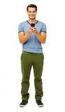 Versenden von SMS-Nachrichten des gutaussehenden Mannes am intelligenten Telefon Stockbild