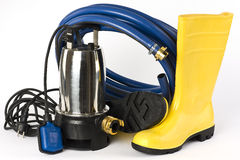 Versenkbare Pumpe, Gummistiefel und Wasser bespritzt mit einem Schlauch Stockbild