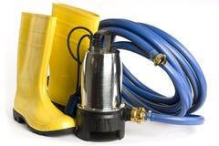 Versenkbare Pumpe, Gummistiefel und Wasser bespritzt mit einem Schlauch Lizenzfreies Stockbild