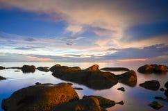 Versenkte Felsen im Meer unter roten Himmeln lizenzfreie stockfotografie