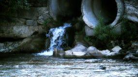 Verseuchtes Wasser von den Kanalisationsrohren verunreinigt klaren Fluss Stockfotos
