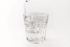 Versez l'eau dans un verre avec éclabousse sur un fond blanc Photographie stock libre de droits