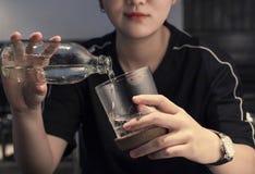 Versez l'eau dans une tasse images libres de droits