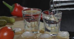 Versez la vodka d'une bouteille dans des verres à liqueur avec des glaçons sur la table photographie stock
