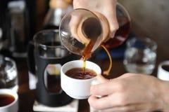 Versez le café fraîchement préparé d'une cruche en verre sur haut étroit de tasses blanches Photos libres de droits