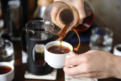 Versez le café fraîchement préparé d'une cruche en verre sur haut étroit de tasses blanches Photographie stock libre de droits